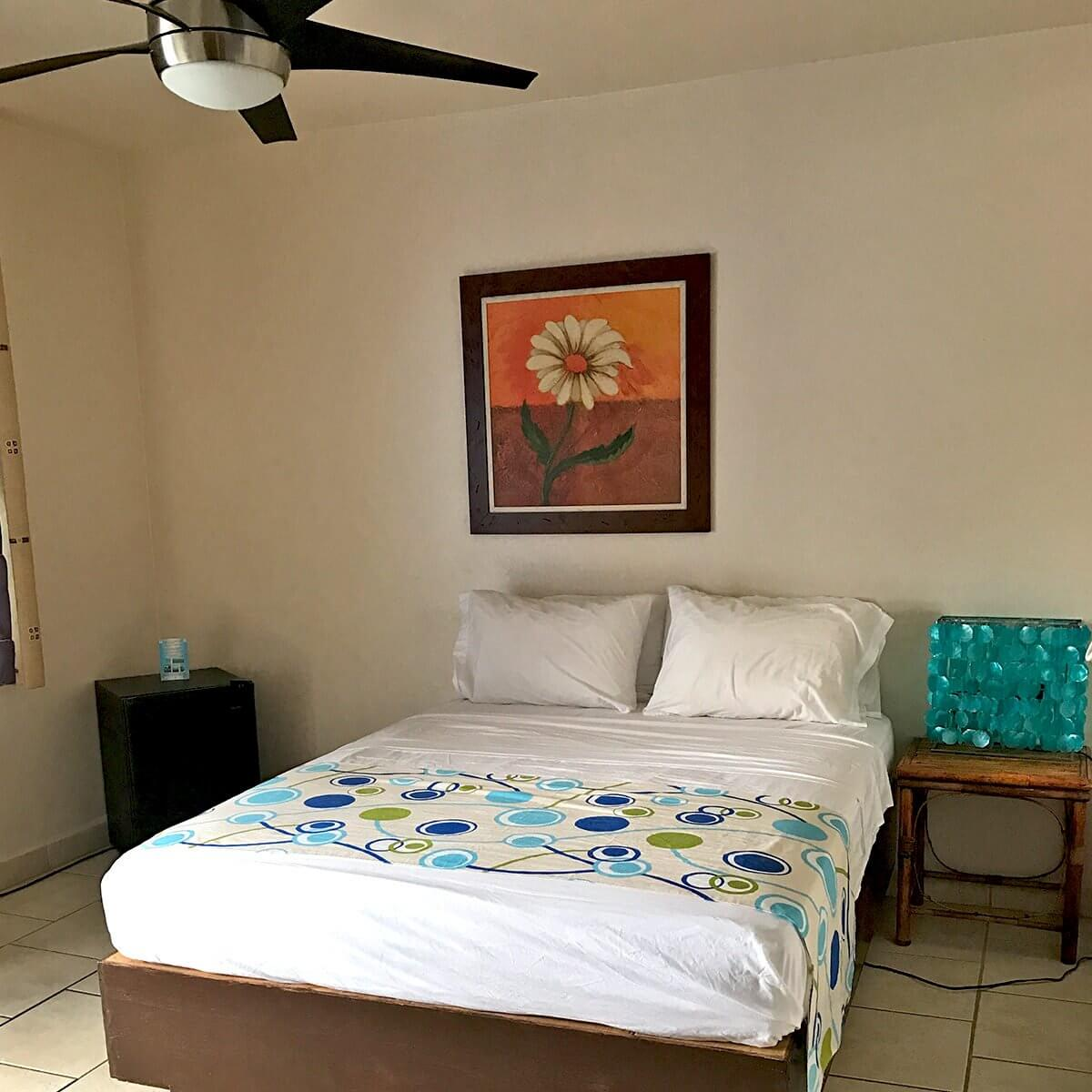 Villa Boheme Guest Room #8 - Queen bed with ceiling fan, mini fridge and nightstand with sparkly lamp.